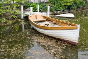 A wooden boat by a lake in a park